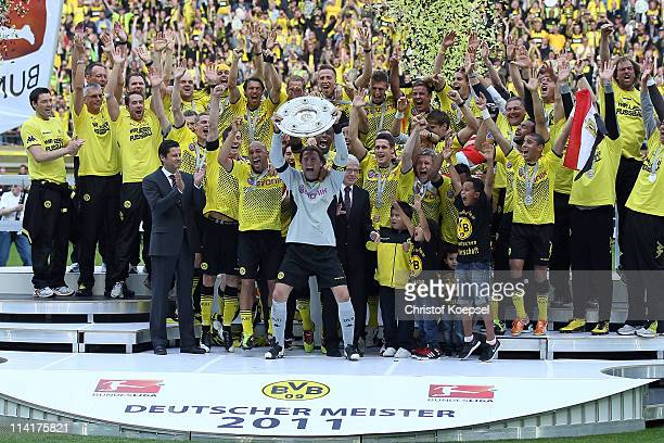 Roman Weidenfeller of Dortmund lifts the German Championship trophy on the podium after the Bundesliga match between Borussia Dortmund and Eintracht...