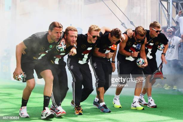 Roman Weidenfeller Shkodran Mustafi Andre Schuerrle Miroslav Klose Mario Goetze and Toni Kroos celebrate on stage at the German team victory ceremony...