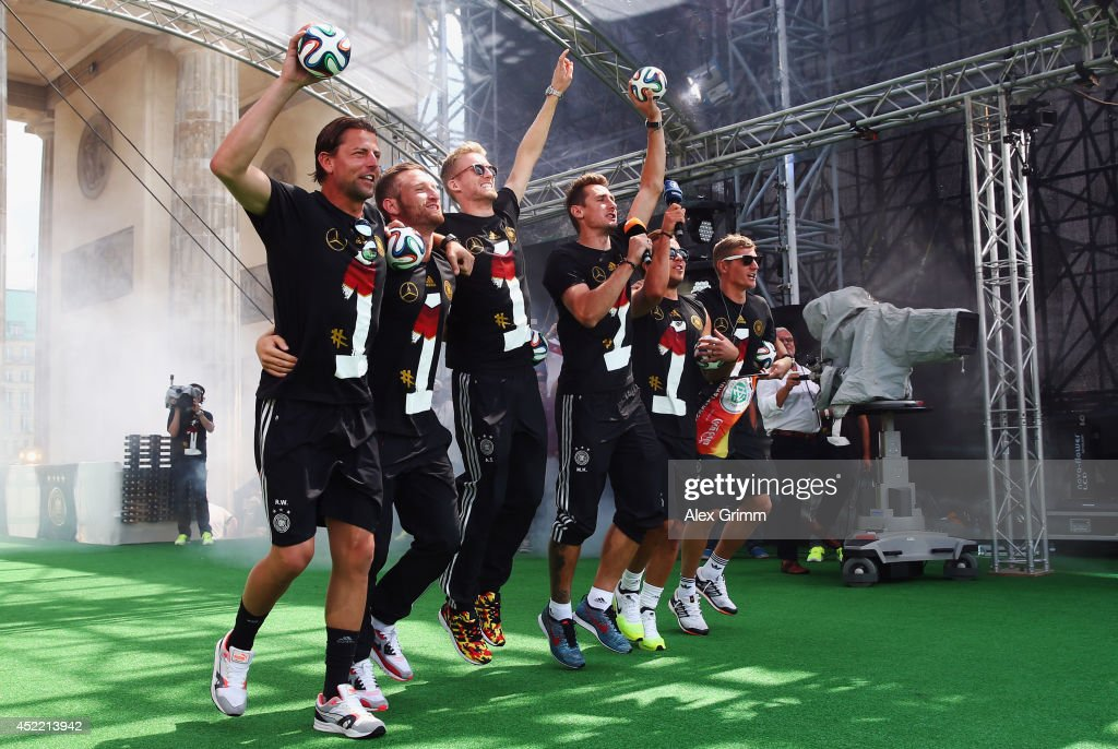 Roman Weidenfeller, Shkodran Mustafi, Andre Schuerrle, Miroslav Klose, Mario Goetze and Toni Kroos (L-R) celebrate on stage at the German team victory ceremony July 15, 2014 in Berlin, Germany. Germany won the 2014 FIFA World Cup Brazil match against Argentina in Rio de Janeiro on July 13.