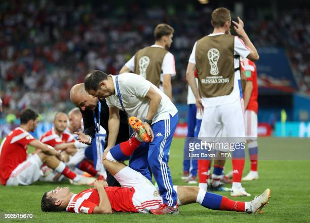Roman Zobnin of Russia recieves treatment for cramp before extra time during the 2018 FIFA World Cup Russia Quarter Final match between Russia and...