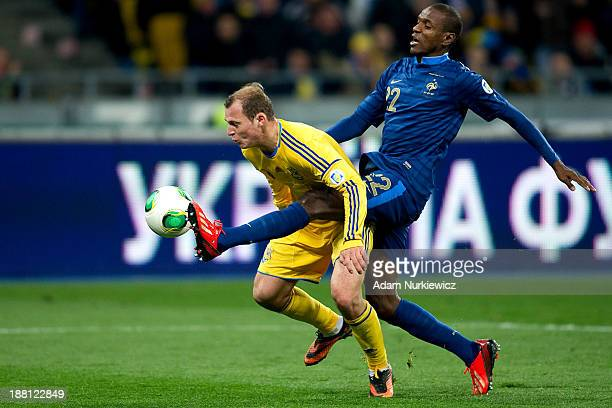 Roman Zozulya of Ukraine fights for the ball with Eric Abidal of France during the FIFA 2014 World Cup Qualifier Playoff First Leg between Ukraine...