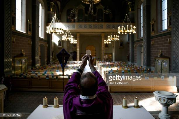 RomanCatholic priest Johannes Laichner leads mass in front of photographs of members of his congregation during the coronavirus crisis in Tyrol...