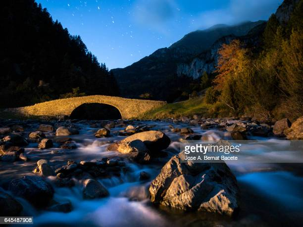 Romanesque Bridge on a river of high mountain in autumn, one night in the moonlight