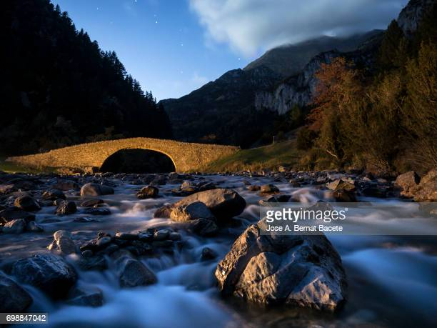 Romanesque Bridge on a river of high mountain in autumn, one night in the moonlight, Bujaruelo Valley, Ordesa-Monte Perdido National Park.
