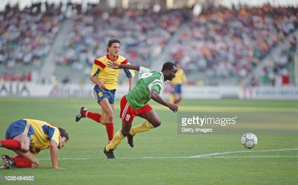 Romania defender Gheorghe Popescu looks on as Cameroon substitute Roger Milla races through to score his first goal during the FIFA 1990 World Cup...