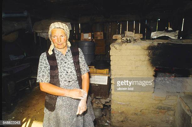 Romania: Local people in the village of Logic. A woman in her kitchen with a oven.