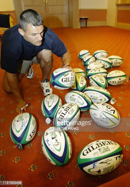 Romania scrumhalf Iulian Andrei signs rugby balls before his team annoucement for their game in Launceston Tasmania for the Rugby World Cup 2003 28...