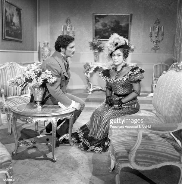Romanian actress Nadia Gray sitting on a sofa meets Fausto Tozzi italian actor in role of composer Gaetano Doninzetti Film Casta Diva directed by...