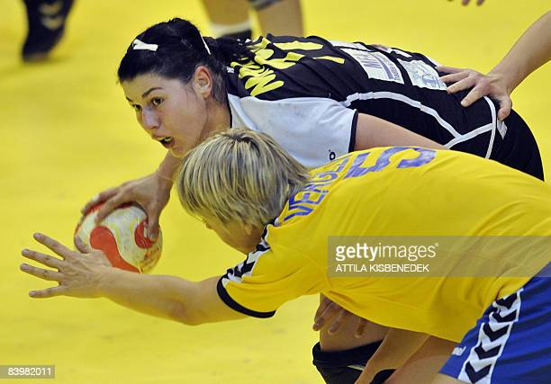 Romanian Andeea Manea fights for the ball with Ukrainian Maryna Vergelyuk during the 8th Women's Handball European Championships match on December 10...