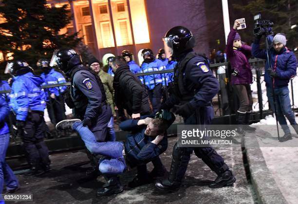 TOPSHOT Romanian antiriot police evacuate a protester during a demonstration against controversial decrees to pardon corrupt politicians and...