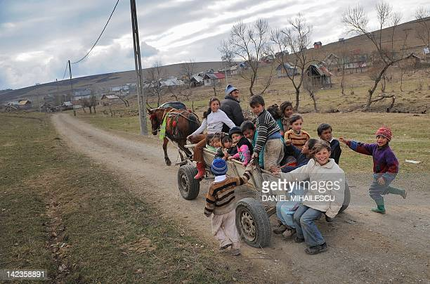Romanian children members of the Roma community are carried by a horse pulled cart back to their homes seen in the background at the end of their...