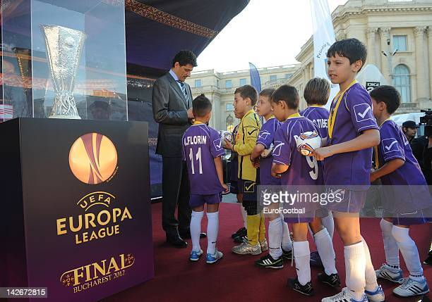 Romanian children receive autographs from former football player Miodrag Belodedici next to the trophy displayed in George Enescu square after UEFA...