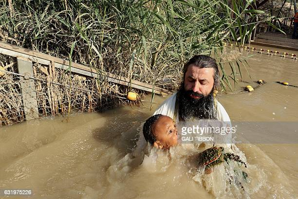 A Romanian Christian Orthodox priest baptizes a pilgrim in the muddy water of the Jordan River during the Epiphany celebrations at the Qasr alYahud...