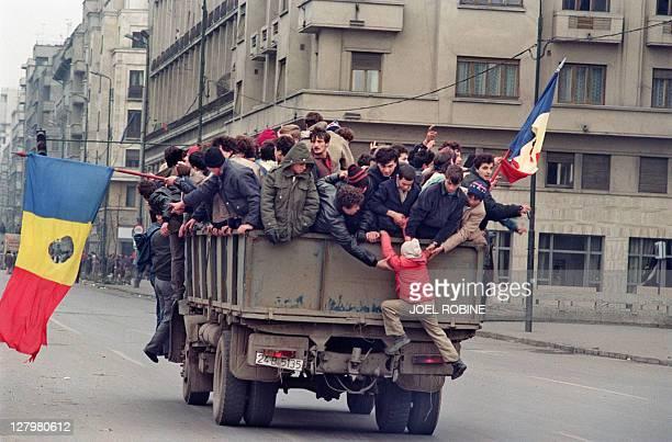 Romanian civilians cross Bucharest on a truck waving flags where the communist symbol has been cut off on December 24 1989 as the antiCommunist...