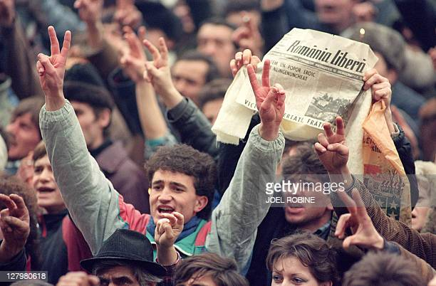 Romanian civilians jubilate during a rally in Bucharest holding newspapers announcing the arrest of Nicolae Ceaucescu on December 24 1989 as the...