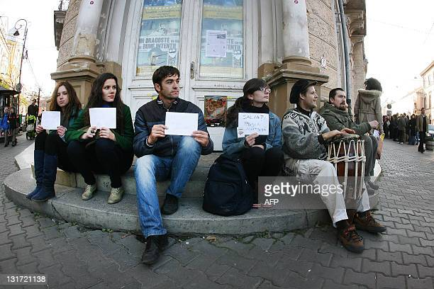Romanian demonstrators hold signs reading Save Rosia Montana during a protest against the Rosia Montana Gold Corporation at the building of the...