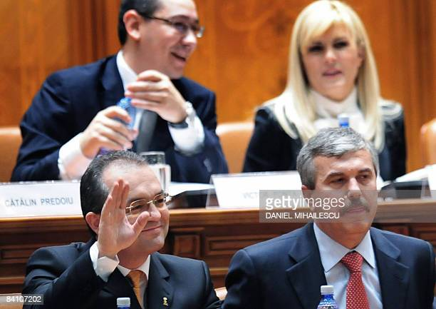 Romanian designated Prime Minister Emil Boc salutes next to his cabinet members as he prepares to address his investiture speech at the Romanian...