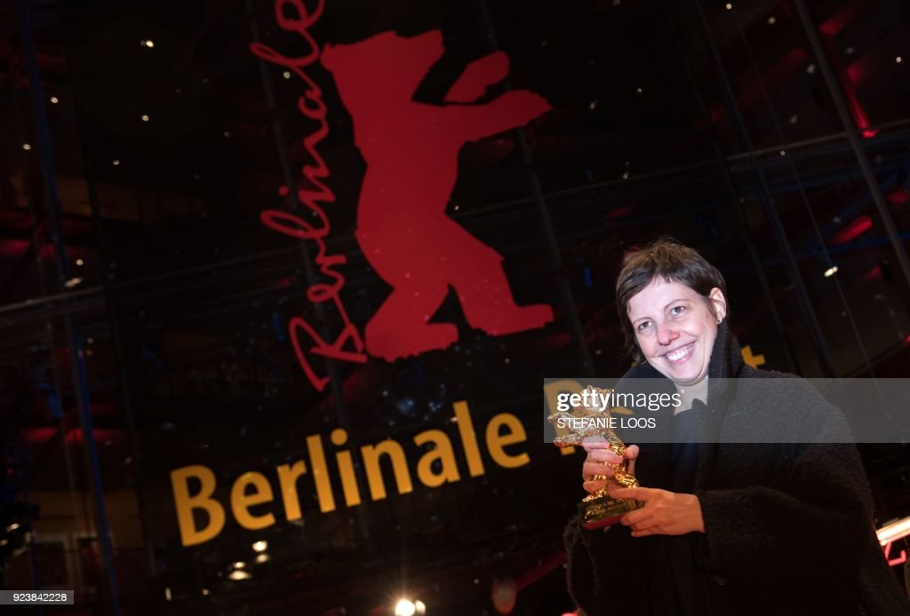 TOPSHOT - Romanian director Adina Pintilie poses with the Golden Bear for Best Film she was awarded for the movie 'Touch Me Not' as she leaves the awards ceremony of the 68th edition of the Berlinale film festival on February 24, 2018 in Berlin. / AFP PHOTO / Stefanie LOOS