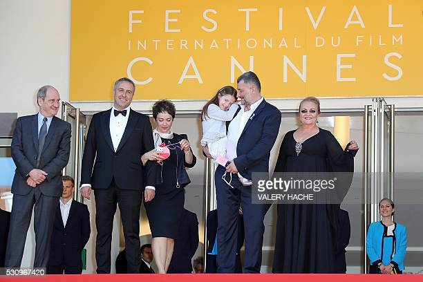 Romanian director Cristi Puiu carries on May 12 2016 his daughter Romanian actress Zoe Puiu while posing with the President of the Cannes Film...