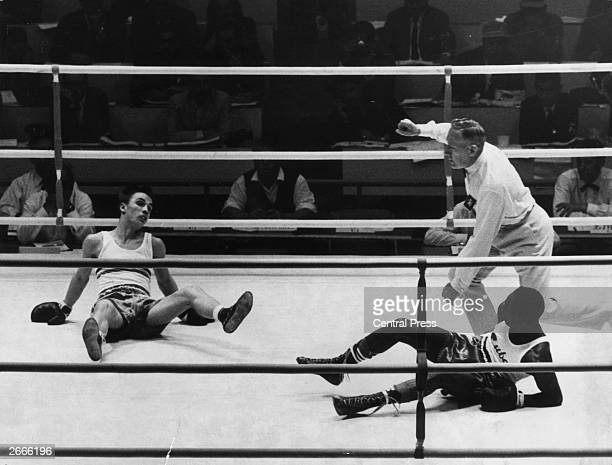 Romanian featherweight boxer Constantin Crudo and his Cuban opponent Roberto Caminero both end up on the canvas during an Olympic boxing match in...