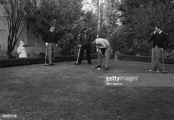 Romanian film director Jean Negulesco plays croquet with guests at his house in Beverly Hills 1952 Actor Louis Jourdan lines up a shot watched by...