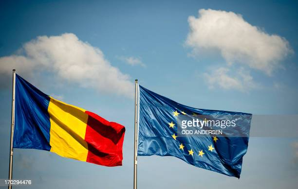 A Romanian flag flies nexto to an EU flag as German Chancellor meets with Romanian prime at the Chancellery in Berlin on June 10 2013 AFP PHOTO / ODD...