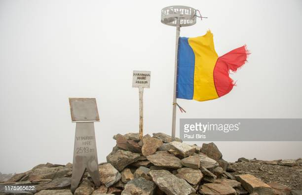 romanian flag on peak parangul mare , southern carpathians, romania - nationaal monument beroemde plaats stockfoto's en -beelden
