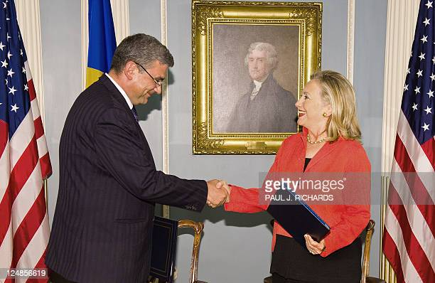 Romanian Foreign Minister Teodor Basconschi and US Secretary of State Hillary Clinton shake hands after signing a Ballistic Missile Defense Agreement...