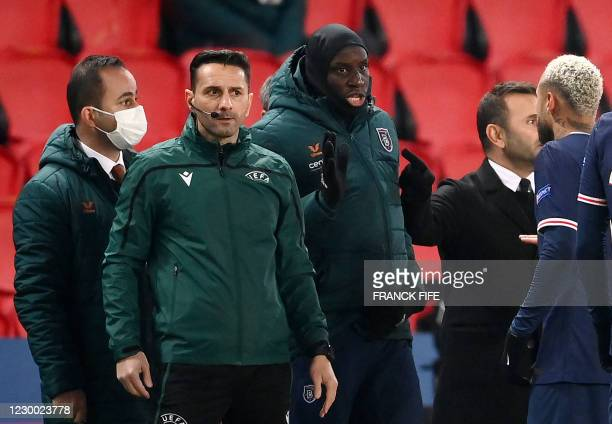 Romanian fourth official Sebastian Coltescu looks on next to Istanbul Basaksehir's French forward Demba Ba and Paris Saint-Germain Brazilian forward...