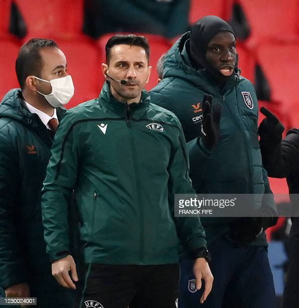 Romanian fourth official Sebastian Coltescu looks on next to Istanbul Basaksehir's French forward Demba Ba during the UEFA Champions League group H...