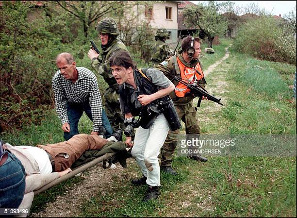 Romanian freelance photographer Vadim Ghirda and locals carry 20 April 1996 a dead Bosnian Moslem as Norwegian and Swedish IFOR soldiers return fire...