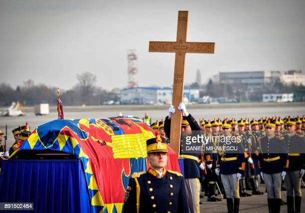 A Romanian guard regiment soldier holds a wooden cross next to the coffin of late King Michael of Romania at Henry Coanda International airport in...