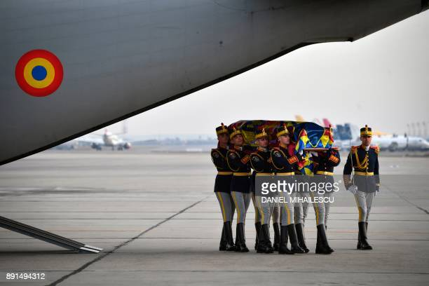 Romanian guard regiment soldiers carry the coffin of late King Michael of Romania at Henry Coanda International airport in Otopeni city next to...