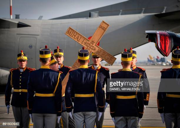 Romanian guard regiment soldiers put the wooden cross of late King Michael of Romania inside a hearse at Henry Coanda International airport in...