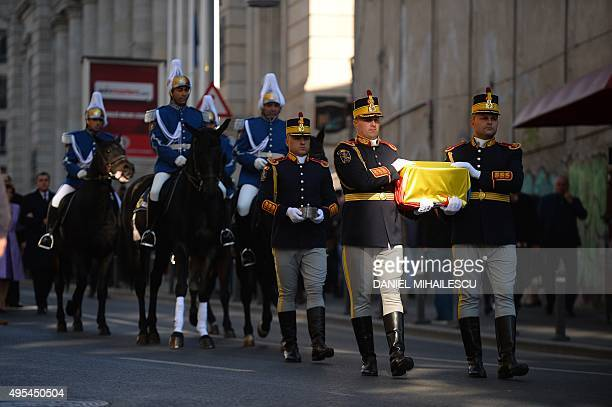 Romanian guard soldiers carry the gilded silver casket containing the heart of the Queen Marie of Romania covered by a national flag on their way to...
