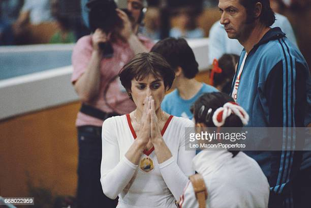 Romanian gymnast Nadia Comaneci pictured talking to a teammate during competition in the women's artistic team allaround competition at the 1980...