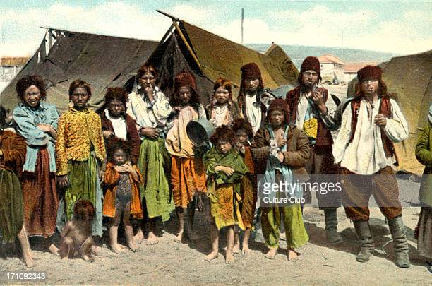 Romanian Gypsies Men women and children Photo by H Wichmann Early 20th century painted photographic postcard