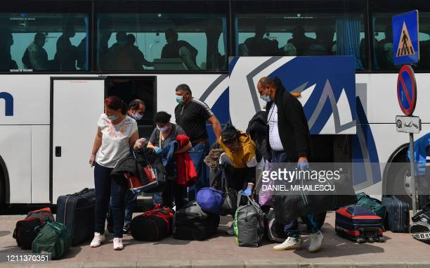 Romanian harvest workers heading to the UK get out of a bus at the Henry Coanda airport in Bucharest April 30 amid the novel coronavirus COVID19...