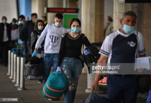 """Romanian harvest workers heading to the UK wait in line to enter the """"Henry Coanda"""" airport in Bucharest April 30 amid the novel coronavirus COVID-19..."""