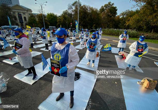 Romanian health workers hold papers bearing the names of their colleagues who died in connection with the pandemic as they protest next to the...