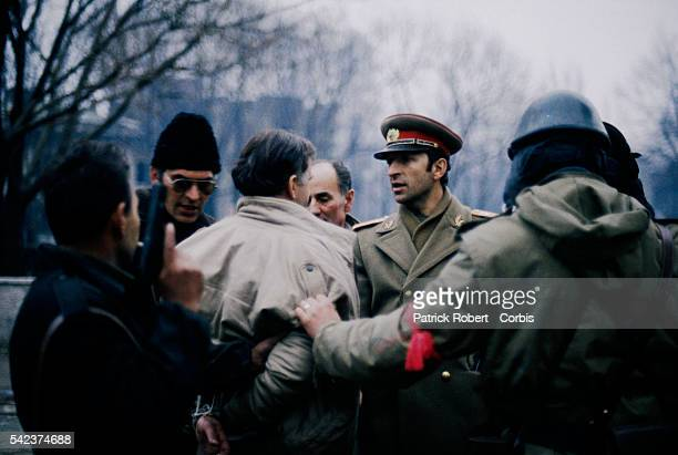 Romanian military officers arrest a man protesting during the December 1989 uprising which marked the end of Communist dictator Nicolae Ceausescu's...
