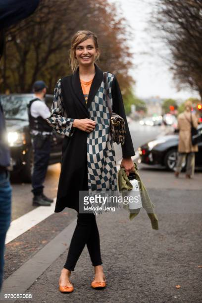 Romanian model Andreea Diaconu wears a checkered scarf and carries a reusable water bottle during Paris Fashion Week Spring/Summer 2018 on October 1...