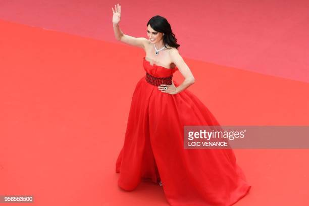 Romanian model Catrinel Menghia waves as she arrives on May 9 2018 for the screening of the film Yomeddine at the 71st edition of the Cannes Film...