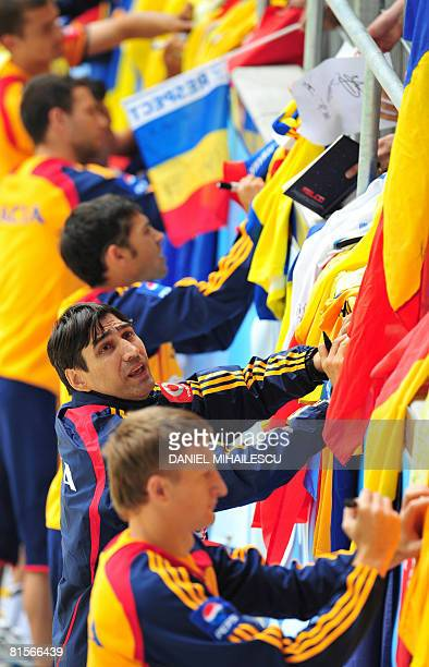 Romanian national football team coach Victor Piturca and players sign autographs to supporters during a training session at AFG Arena stadium on June...