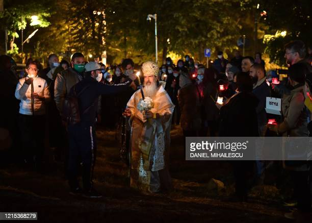 """Romanian Orthodox Archbishop Teodosie shares a """"Holy Light"""", or candle flame to faithful during a second Easter religious service at the Orthodox..."""