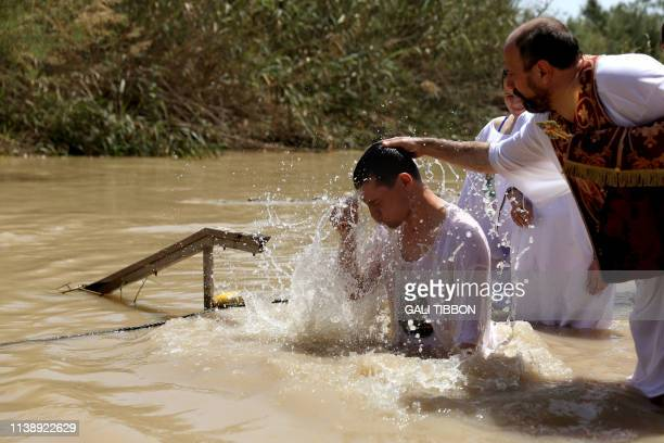 A Romanian Orthodox pilgrim emerges from the waters of the Jordan River after he was baptized on April 23 2019 at the Qasr al Yahud baptismal site...