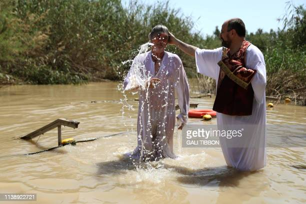 A Romanian Orthodox pilgrim emerges from the waters of the Jordan River after she was baptized on April 23 2019 at the Qasr al Yahud baptismal site...