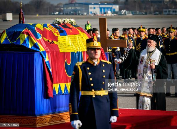 A Romanian orthodox priest holds a religious service next to the coffin of late King Michael of Romania at Henry Coanda International airport in...