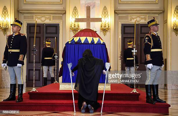 A Romanian pays respect to the late Queen Anne of Romania at the Royal Palace now The Art Museum of Romania in Bucharest August 11 2016 The body of...