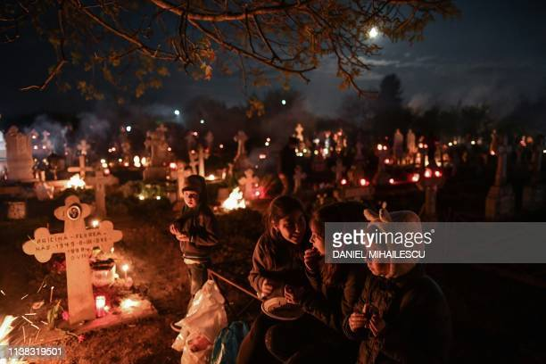 TOPSHOT Romanian people light fires at the graves of their loved ones during Palm Sunday celebration in the village of Herasti south of Bucharest on...